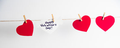Three red paper hearts and one white heart with congratulation and wings fixed with clothespins on a cord. White. Background Royalty Free Stock Photo