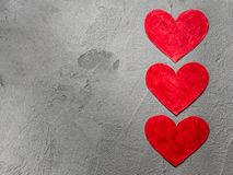 Three Red paper hearts upright on gray wall with copy space. Red paper hearts on gray wall with copy space Happy Valentine background royalty free stock photography