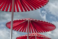 Three red parasols standing outside stock photography