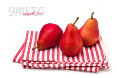 Three red pears on striped tablecloth Stock Images