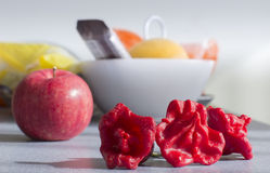 Three red peppers and an apple Royalty Free Stock Image