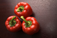 Three red peppers on dark wood Royalty Free Stock Photography