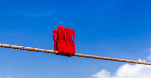 Three red plastic clothespins are on clothesline with blurry blu Stock Photos