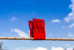 Three red plastic clothespins hang on a laundry line. Stock Photography