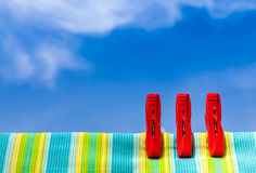 Three red plastic clothespins and multicolor cotton with the blu Royalty Free Stock Photography