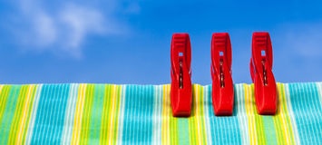 Three red plastic clothespins and multicolor cotton with the blu Stock Photo