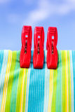 Three red plastic clothespins and multicolor cotton with the blu Royalty Free Stock Image
