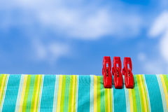 Three red plastic clothespins and multicolor cotton with the blu Stock Image