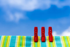 Three red plastic clothespins and multicolor cotton with the blu Stock Images