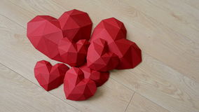 Three red polygonal paper heart shape over wooden bachground stock video