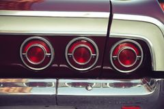 Three red rear tail lights from a vintage retro car with nostagic look. Three red rear tail lights from a vintage retro car. Photo post processed to emphasise an royalty free stock photos