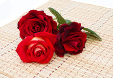 Three red roses are on a bamboo napkin. Three beauty red roses are on a bamboo napkin Royalty Free Stock Photography