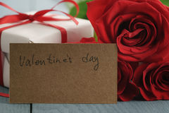 Three red roses on blue wood table with gift and valentines day paper card Royalty Free Stock Photos