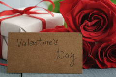 Three red roses on blue wood table with gift and valentines day paper card Royalty Free Stock Images