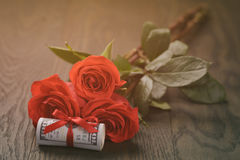 Three red roses and bunch of dollars Royalty Free Stock Photo