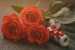 Three red roses and bunch of dollars Royalty Free Stock Images