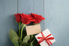 Three red roses with gift on blue wood table with valentines day paper card Stock Image