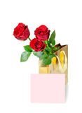 Three red roses in a golden gift bag and note card Royalty Free Stock Image