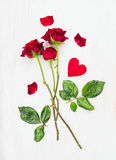 Three red roses on long stems and heart on white wood, love card. Three red roses on long stems and heart on white wood, valentine royalty free stock photo