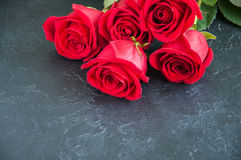 Three red roses over black stone background. Copy space. Close u Stock Photos