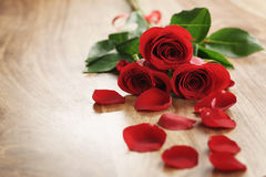 Three red roses and petals on old wood table with copy space Stock Photos
