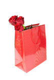 Three red roses in a red gift bag on white background Royalty Free Stock Images