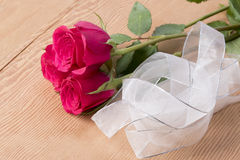 Three red roses with ribbon on wooden background Stock Photo