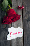 Three red roses on rustic table with handwritten word dream Royalty Free Stock Images