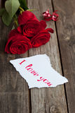 Three red roses on rustic table with handwritten words I love yo Stock Image