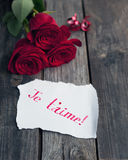 Three red roses on rustic table with handwritten words je t'aime Stock Images