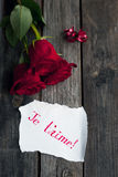 Three red roses on rustic table with handwritten words je t'aime Royalty Free Stock Image