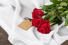 Three red roses on silk fabric Stock Image