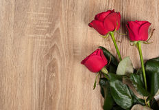 Three red roses on wood Royalty Free Stock Photography