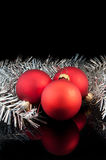 Three red satin Christmas balls. With silver decoration on black background royalty free stock photo