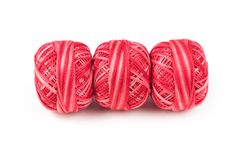 Three red sewing threads in a row on a white background Royalty Free Stock Photos