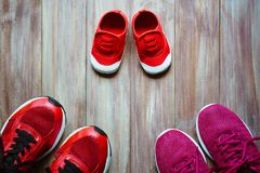 Three red sport running shoes or sneakers of mother and father a. Nd child on wooden background,use for father`s day or mother`s day or family`s day with sport Royalty Free Stock Photo