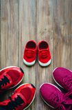 Three red sport running shoes or sneakers of mother and father a. Nd child on wooden background,use for father`s day or mother`s day or family`s day with sport Stock Image
