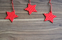 Three red stars on wooden background Stock Image