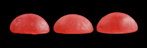 Three red Swedish candy pieces isolated on black background Stock Photo