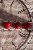 Three red sweets in the shape of a heart on a lace ribbon on the old decorative paper. Postcard or background on Valentine`s Day Stock Photography