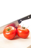 Three red tomatoes and a steel knife Royalty Free Stock Photos