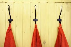 Three red towels on hangers on yellow wooden wall royalty free stock images