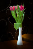 Three red tulips in a white vase Stock Photos