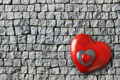 Three red Valentines day hearts on an background of old grey cobblestone bricks royalty free stock photos