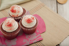 Three red velvet cupcakes on colorful paperbag Royalty Free Stock Photo
