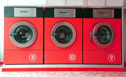 Three red washing machines in coin laundry Royalty Free Stock Images