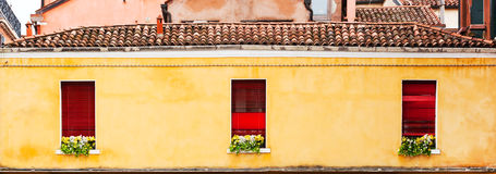 Three red windows with flowers of a typically Italian house. Royalty Free Stock Image