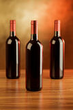 Three red wine bottles on wooden table and golden background Royalty Free Stock Photography