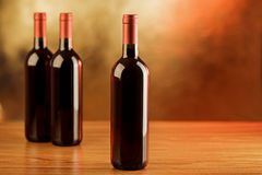Three red wine bottles on wooden table and golden background Stock Photo