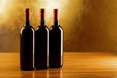Three red wine bottles on wooden table and golden background Royalty Free Stock Images